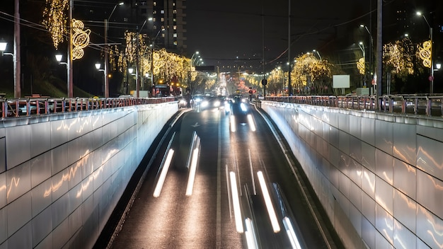 Paisagem urbana da cidade à noite, vários carros se movendo na estrada dentro de um túnel, muita iluminação de natal, traços de luz em bucareste, romênia