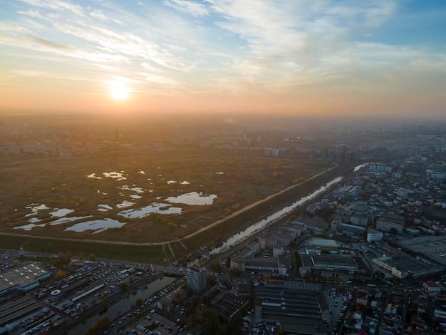 Paisagem urbana de bucareste ao pôr do sol, várias áreas verdes e lagos em um parque e edifícios residenciais. vista do drone, vista panorâmica, romênia