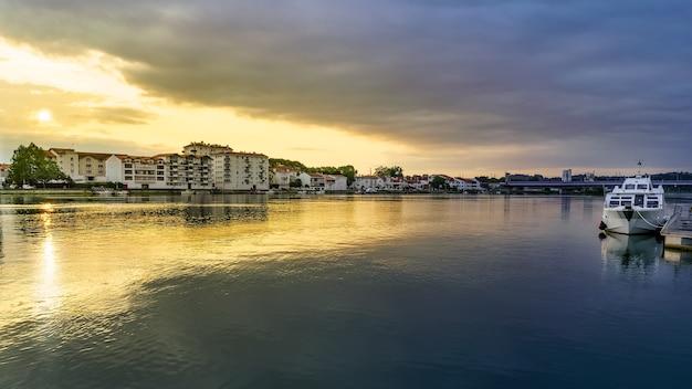 Paisagem urbana em bayonne, frança, com o barco do rio adur navegável. pôr do sol sobre o rio. vista panorâmica.