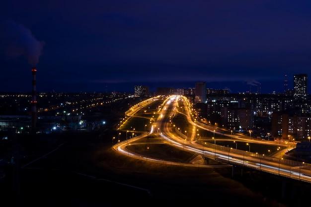 Paisagem urbana noturna com entroncamento rodoviário iluminado, edifícios residenciais e uma zona industrial com chaminé