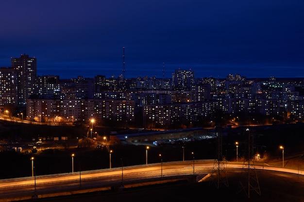 Paisagem urbana noturna com uma estrada iluminada em primeiro plano e áreas residenciais de vários andares ao fundo