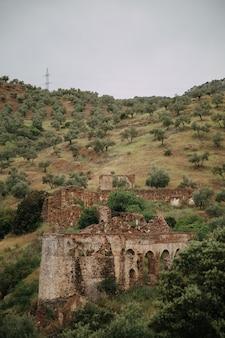 Paisagem verde com altas montanhas e ruínas de edifícios destruídos