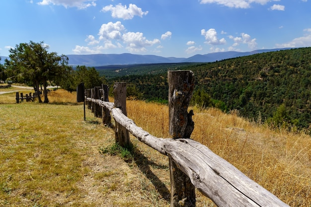 Paisagem verde com cerca de madeira, prados de grama e florestas de árvores, céu azul com nuvens. espanha.