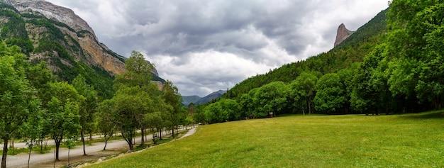 Paisagem verde panorâmica com árvores, grama e nuvens escuras em um dia nublado de verão em ordesa pirineos