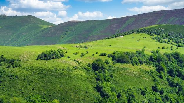 Paisagem verde panorâmica de altas montanhas com pequena casa no topo da colina. santander.