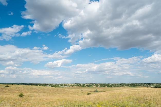Paisagem vila luz do dia país, nuvens do céu azul, colinas de campo