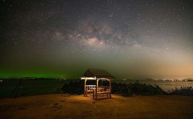 Paisagem vista do mar imagem da vista da natureza da incrível galáxia da via láctea sobre o mar com cabana de bambu em primeiro plano no céu noturno em phuket, tailândia.