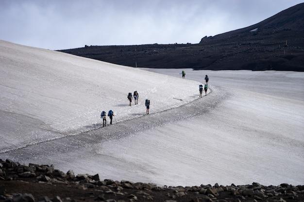 Paisagem vista glaciar com grupo de caminhantes com mochila caminhando na geleira. islândia.