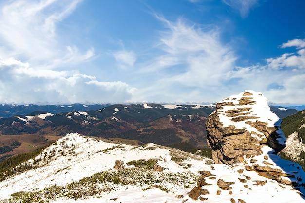 Paisagens maravilhosas cobertas pela primeira neve com grandes saliências rochosas das montanhas dos cárpatos, céu azul claro na pitoresca ucrânia perto da vila de dzembronya
