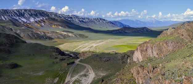Paisagens secas da mongólia nas montanhas de altai. estrada rural no vale, contraste de luz e sombra.