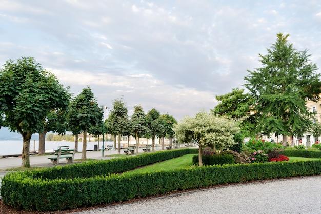 Paisagismo do aterro da cidade com árvores aparadas, arbustos e canteiros de flores.