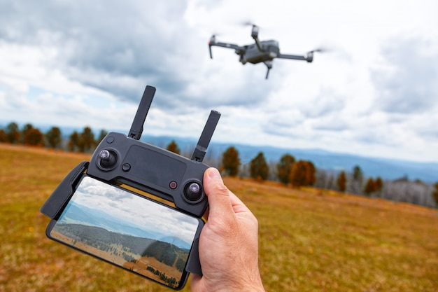 Paisagismo em um zangão. um jovem tem na mão um painel de controle quadrocopter com um monitor e uma imagem de montanhas