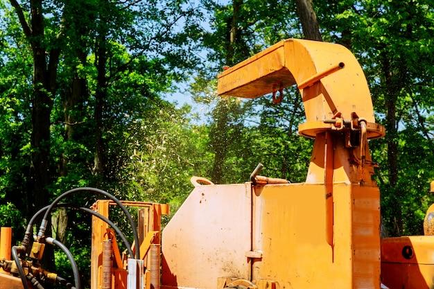 Paisagistas usando máquina chipper para remover e transportar galhos de árvores motosserra