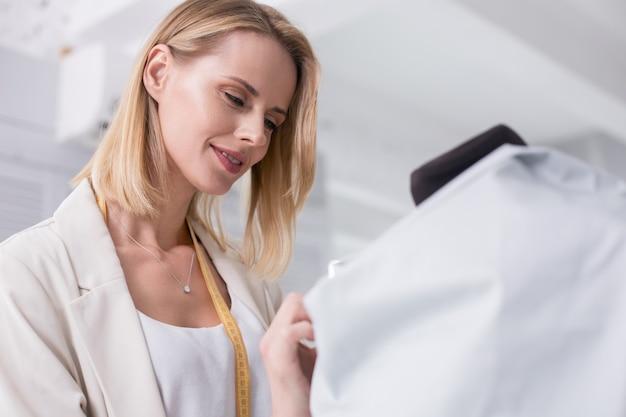 Paixão pelo trabalho. ângulo baixo de alfaiate feminina satisfeita trabalhando com tecido enquanto sorri