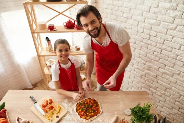 Paizinho de sorriso com a filha que cozinha a pizza em casa.