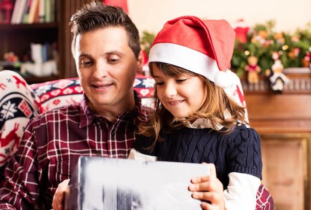 Paizinho e filha abrindo presentes de um natal