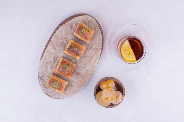 Pakhlava turco na bandeja de madeira com confiture e uma xícara de chá.