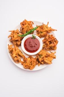 Pakora de cebola frita ou pyaj pakoda, também conhecido como crispy kanda bhaji / bhajji / bajji, lanche da hora do chá indiano favorito durante a estação das chuvas. servido com ketchup de tomate