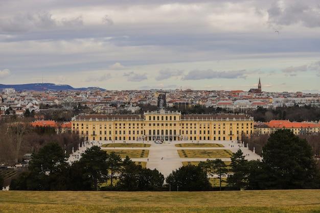 Palácio de schönbrunn muito colorido entre o céu e a grama em um dia nublado.