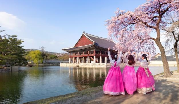 Palácio gyeongbokgung com vestido nacional coreano e flor de cerejeira na primavera, seul, coréia do sul.