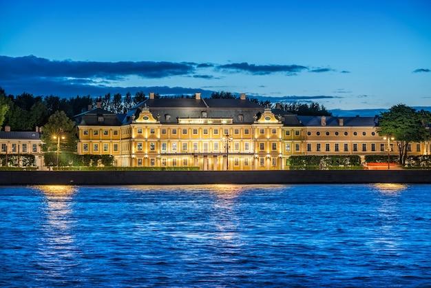 Palácio menshikov no aterro da universidade na iluminação noturna nas margens do rio neva em são petersburgo em uma noite azul de verão