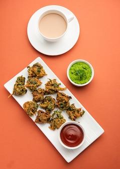 Palak saboroso caseiro pakoda ou pakora conhecido como spinach firtters, servido com ketchup. lanche da hora do chá favorito da índia
