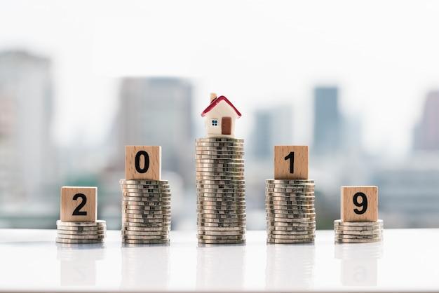 Palavra 2019 do bloco de madeira ano novo e casa sobre a pilha das moedas.