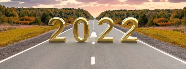 Palavra 2022 na estrada de asfalto vazia ao pôr do sol dourado e lindo céu. conceito para o ano de visão 2022