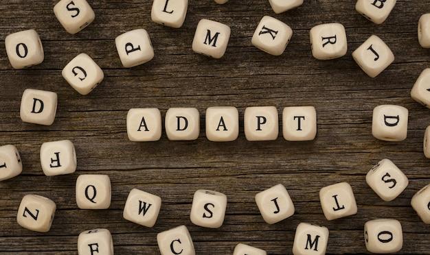 Palavra adapt escrita em bloco de madeira