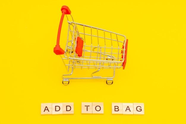 Palavra adicionar à sacola feita de cubos de madeira em fundo amarelo com carrinho de compras de brinquedos