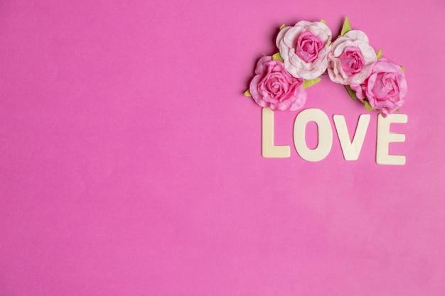 Palavra amor em corações vermelhos em fundo rosa, ícone de amor, dia dos namorados, conceito de relações