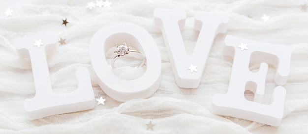 Palavra amor em tecido branco com anel de noivado de diamante. bom para cartões de dia dos namorados.
