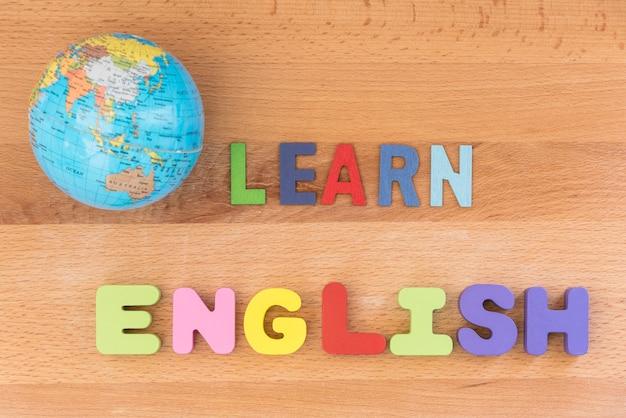 Palavra aprende inglês com globo sobre fundo de madeira