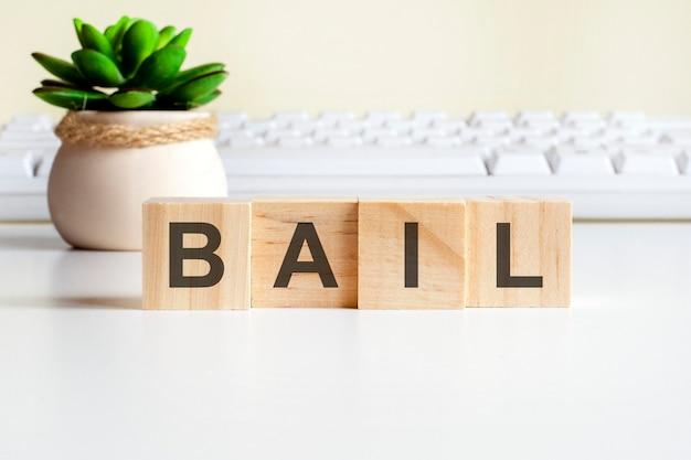 Palavra bail feita com blocos de madeira. conceitos de vista frontal, planta verde em um vaso de flores e teclado branco no fundo
