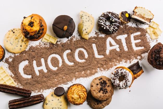 Palavra chocolate em gotas de chocolate entre doces