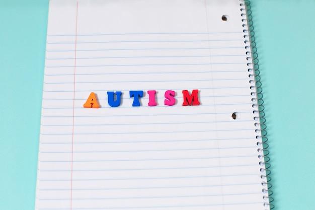 Palavra colorida do autismo das letras de madeira da cor na página do caderno.