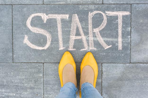 Palavra começa no asfalto e pés mulher