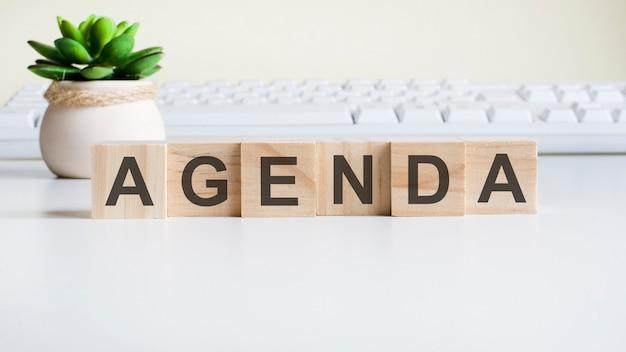 Palavra da agenda feita com blocos de madeira. conceitos de vista frontal, planta verde em um vaso de flores e teclado branco no fundo