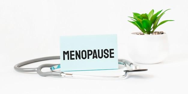 Palavra da menopausa no caderno, estetoscópio e planta verde