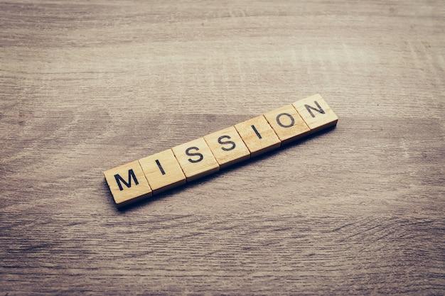 Palavra da missão na mesa de madeira para o conceito de negócio.