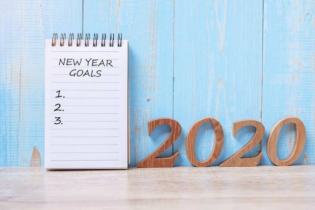 Palavra de 2020 objetivos de ano novo feliz no caderno e número de madeira.