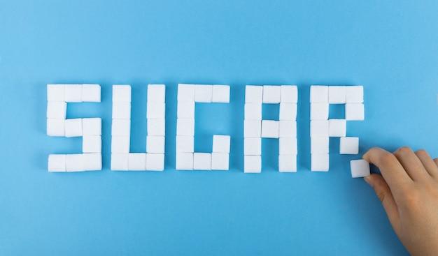 Palavra de açúcar feita de cubos de açúcar branco na superfície azul. vista superior de cubos de açúcar de cana não refinado