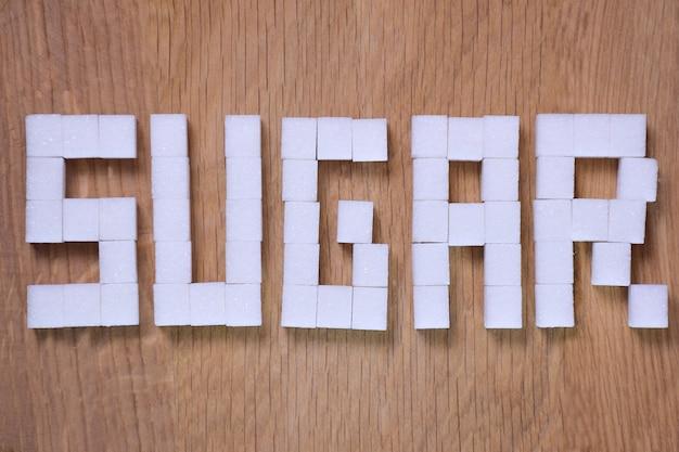 Palavra de açúcar forrada com cubos de açúcar refinado em close-up de fundo marrom de madeira