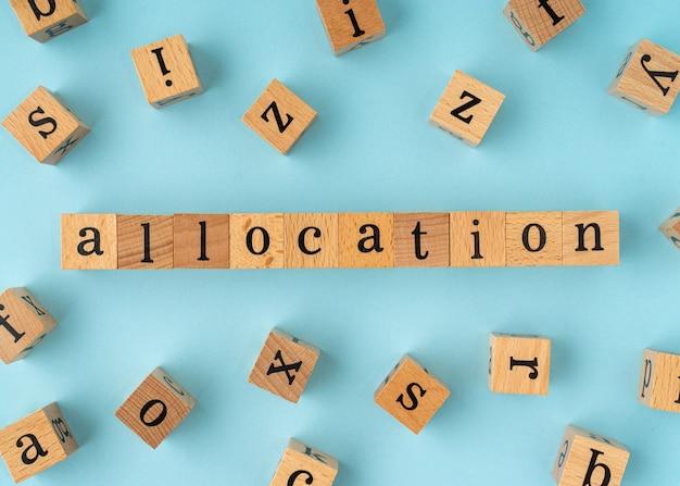Palavra de alocação em bloco de madeira. vista plana leiga sobre fundo azul.
