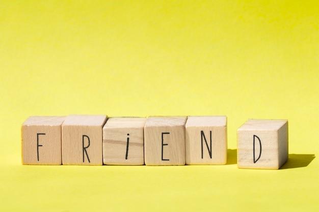 Palavra de amigo em cubos de madeira com design retrô de fundo amarelo conceito de amigo moderno