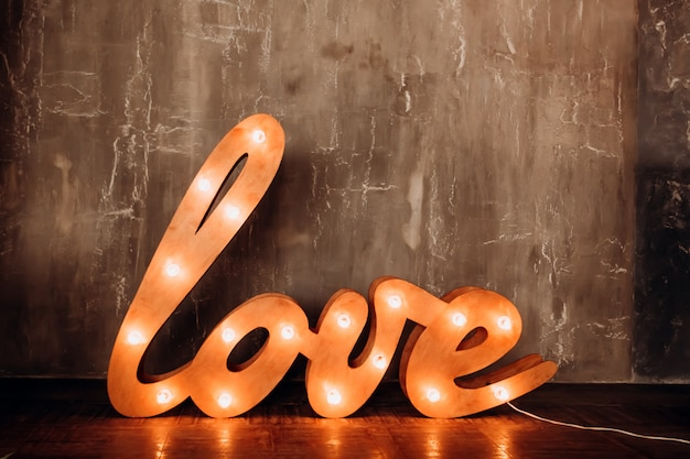 Palavra de amor. cartas com lanternas. a palavra brilhante amor no interior. letras enormes com lâmpadas permanecem no chão.