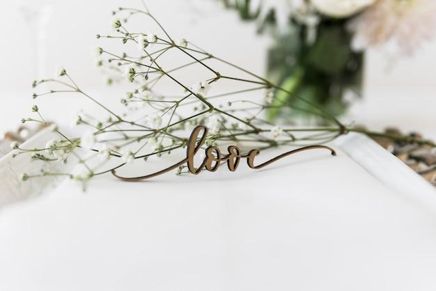 Palavra de amor e flores brancas na placa