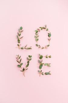 Palavra de amor feita de galhos de eucalipto em fundo rosa. camada plana, vista superior.