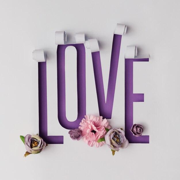 Palavra de amor feita de papel rasgado em fundo violeta com várias flores.
