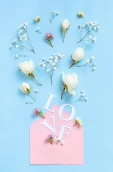 Palavra de amor, flores e envelope rosa em uma vista superior de fundo azul claro